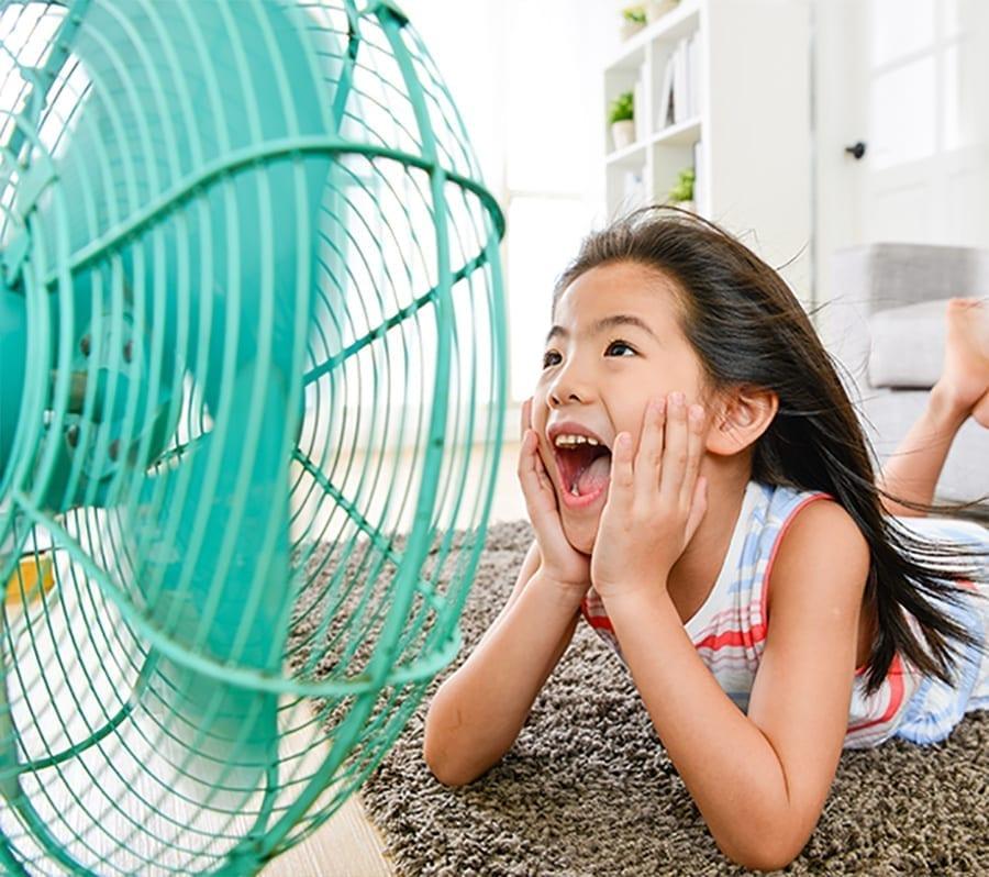 little girl in front of fan